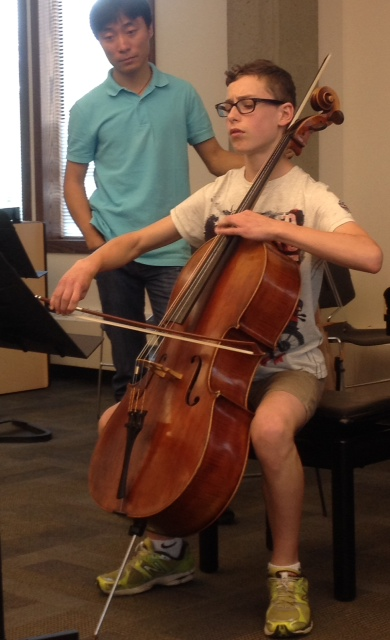 Cellist Tian Bonian instructs Winnipeg student David Liam W. during a master class at Morningside Music Bridge.